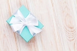 Gift box with bow over white wooden table