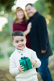 Mixed Race Boy Holding Gift In Front with Parents Behind