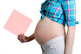Pregnant beautiful young woman with blank post-it note. All on w