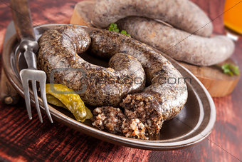 Blood sausage and rice sausage on wooden background.