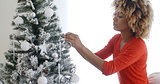 Attractive African woman decorating the Xmas tree
