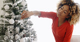 Pretty young African woman decorating an Xmas tree