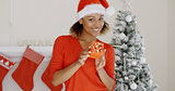 Lovely young woman holding a Christmas gift