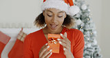 Excited young woman looking at a Christmas gift