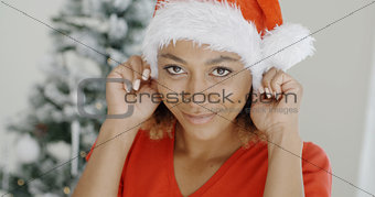 Attractive young woman donning a Santa hat