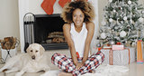 Cute young woman and her dog at Christmas