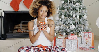 Blissful young woman drinking coffee at Christmas