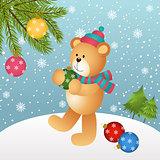 Teddy bear placing glass balls in Christmas tree