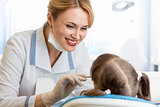 smiling dentist woman examining kid patient in clinic