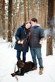 Happy Couple with Dog Enjoying Winter Evening