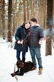 Happy Couple with Dog Enjoying Winter Evening