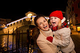 Laughing mother and daughter in Christmas decorated Venice