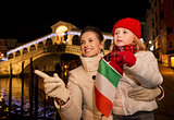 Daughter and mother with Italian flag in Christmas Venice, Italy