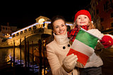 Mother and daughter showing Italian flag in Christmas Venice