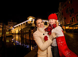 Mother and daughter pulling gift from Christmas sock in Venice