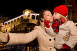 Daughter kissing mother taking selfie in Christmas Venice, Italy
