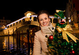 Woman holding Christmas tree near Rialto Bridge in Venice, Italy