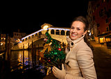 Happy woman with Christmas tree near Rialto Bridge in Venice
