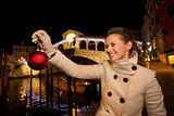 Young woman holding Christmas Ball near Rialto Bridge in Venice