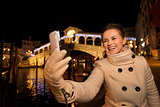 Woman taking selfie near Rialto Bridge in Christmas Venice