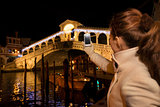Woman taking photo of Rialto Bridge in Christmas Venice, Italy