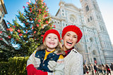 Portrait of mother and daughter near Christmas tree in Florence