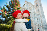 Mother and daughter hugging near Christmas tree in Florence