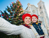 Mother and daughter taking selfie near Christmas tree, Florence