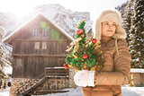 Young woman with Christmas tree standing near mountain house