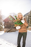 Woman with Christmas tree showing thumbs up near mountain house