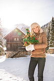Happy woman with Christmas tree standing near mountain house