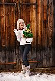 Woman with Christmas tree near rustic wood wall handwaving