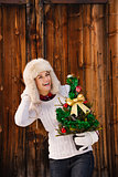 Happy woman holding Christmas tree and looking on something