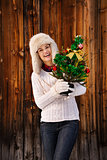 Happy woman with Christmas tree in the front of rustic wood wall