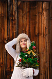 Dreamy woman with Christmas tree in front of rustic wood wall