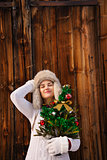 Relaxed woman with Christmas tree in front of rustic wood wall