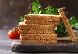 toasted rye bread with vegetables and herbs on a wooden board