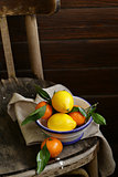 citrus fruit tangerines and lemons on the old vintage chair