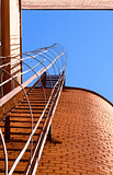 Industrial ladder, blue sky and brick walls of the building