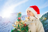 Happy young woman with Christmas tree in the front of mountains