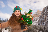 Woman with Christmas tree taking selfie in front of mountains