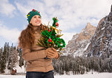 Smiling woman holding Christmas tree in the front of a mountains
