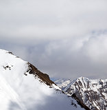 Snowy slope and sky with clouds at sun day