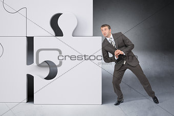 Man in suit pushing puzzle piece