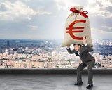 Businessman holding heavy moneybag with euro sign