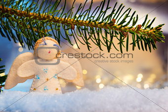 branch, felt angel on snow and bokeh lights