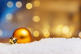 Golden bauble on snow