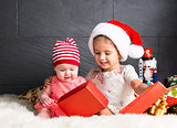Cute kids on rug opening a Christmas present
