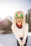 Young woman in a Christmas glasses in front of a mountain house