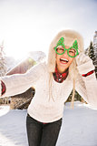 Woman in Christmas glasses taking selfie near a mountain house